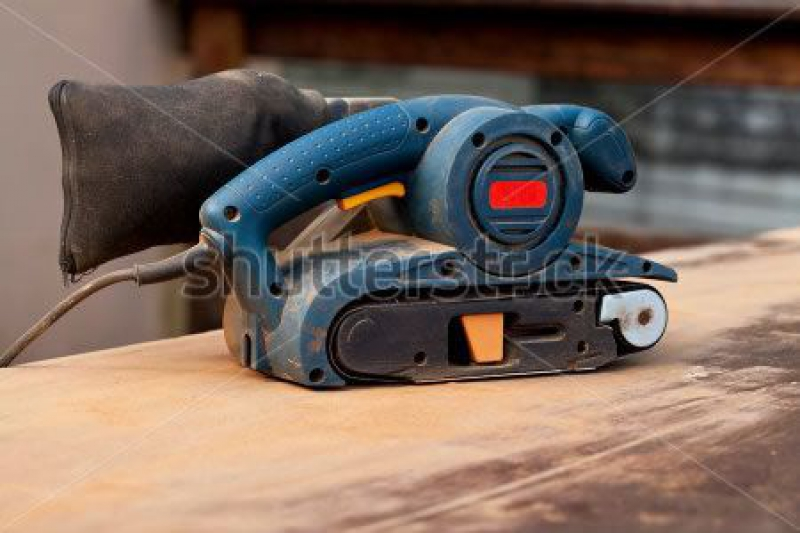 stock-photo-a-belt-sander-tool-on-a-wooden-surface-with-saw-dust-145174996